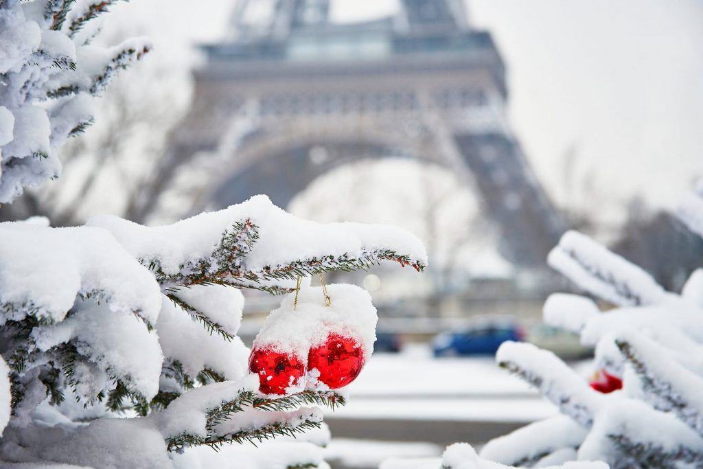 Christmas tree decorated with red balls and covered with snow on a rare snowy day in Paris. Eiffel tower is in the background